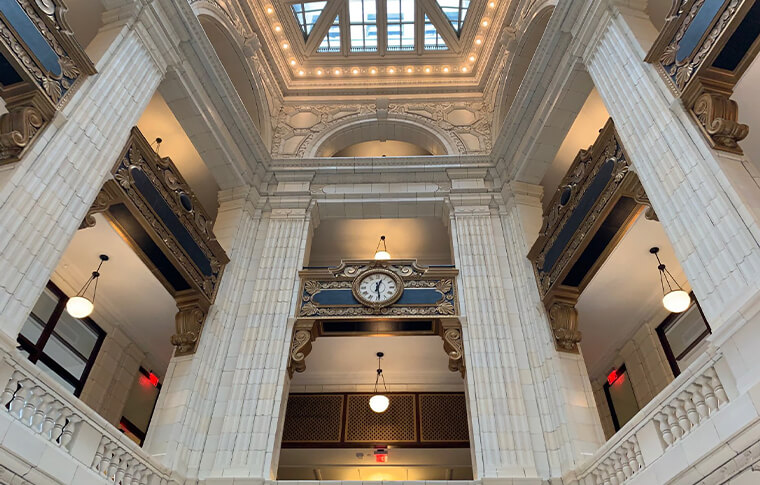 Interior of a tall building with a large clock in the middle and several white columns built into the walls, as well as a sunroof