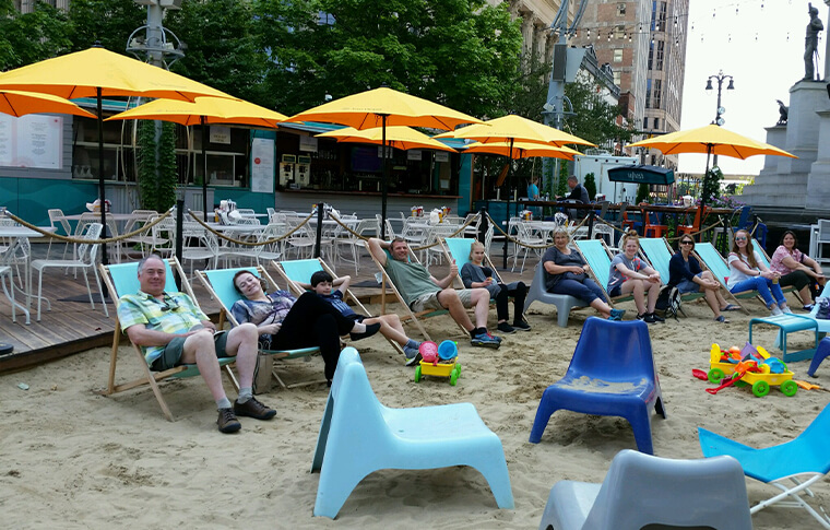 Several people posing in beach chairs near yellow umbrellas in the middle of the city