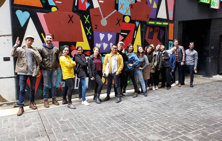 Large group of guests posing in front of a colorful mural made up of of geometric shapes with three figures