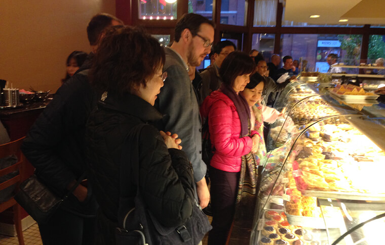 Group of people admiring baked goods behind the glass at a bakery