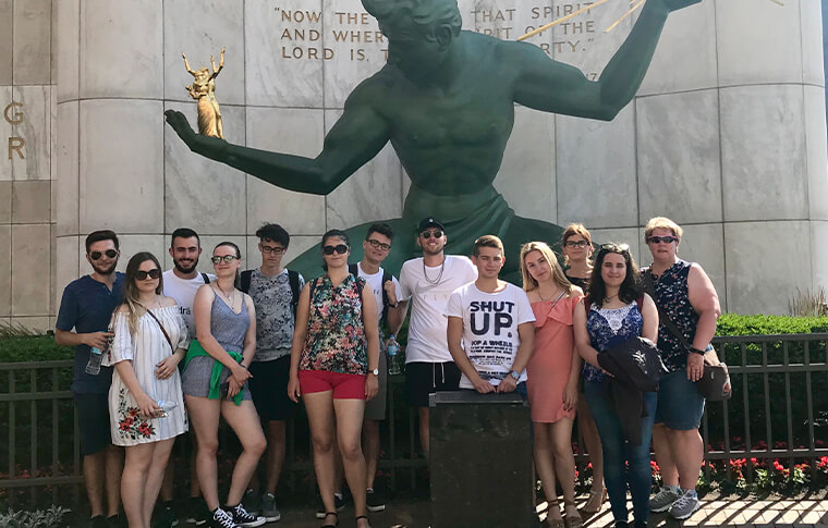 Group of several people posing in front of a green statue with his arms outstretched