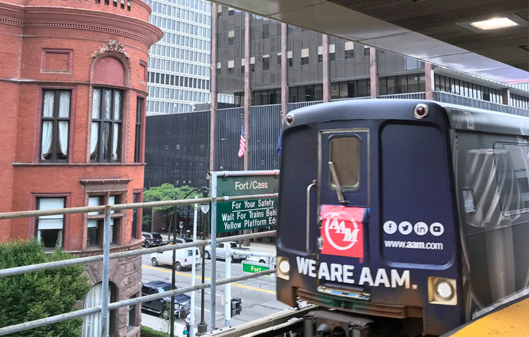 Back of an elevated train car next to an older red brick building and the Fort/Cass sign