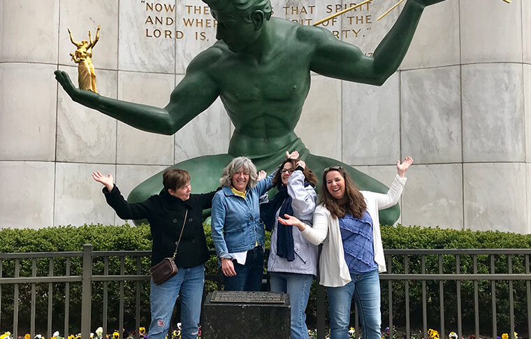 Group of four women posing in front of a large green statue of a man with his arms outstretched