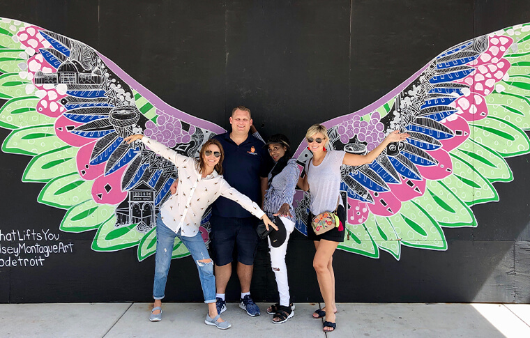 Group of four people posing in front of colorful bird wings painted on a wall