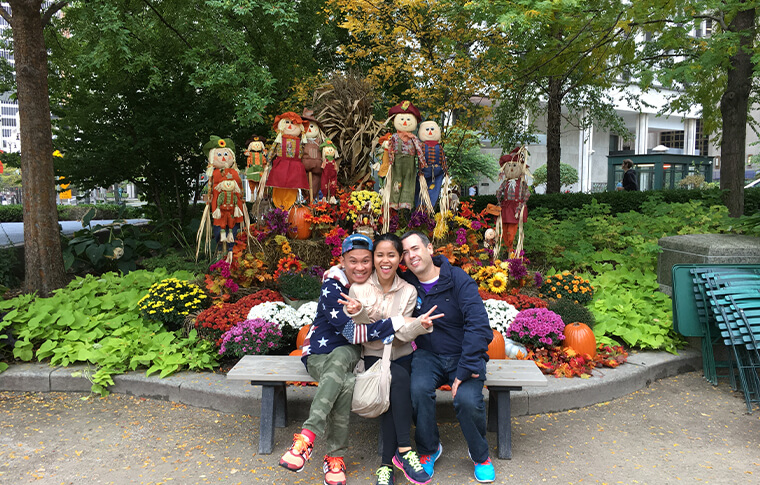 Three guests posing in front of an autumn-themed display