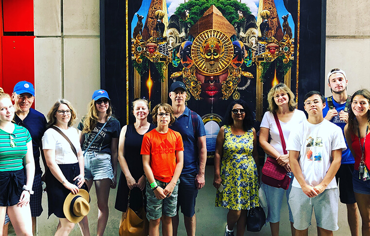 Group of guests posing in front of a colorful piece of artwork
