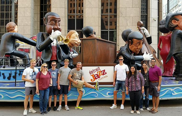 Group of guests posing in front of a float for the Detroit Jazz Festival