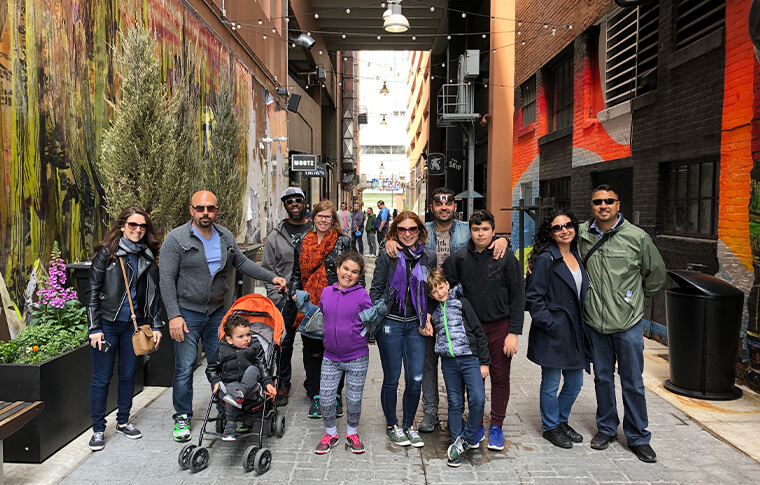 Group of adults and children posing in an alley with a cactus mural on one side and colorful orange and black walls on the other