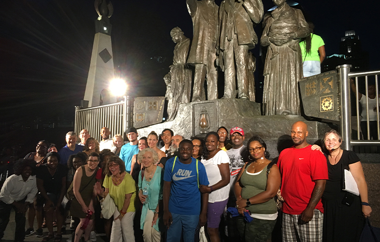Group of people standing in front of a statue to commemorate the Underground Railroad