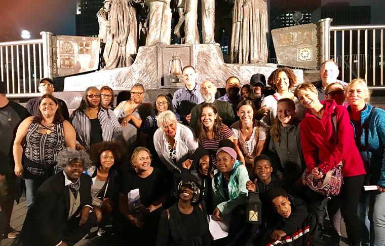 Large group of people posing in front of a statue commemorating the Underground Railroad