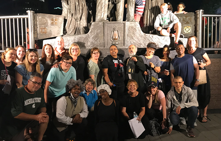Large group of people posing in front of a monument to the Underground Railroad