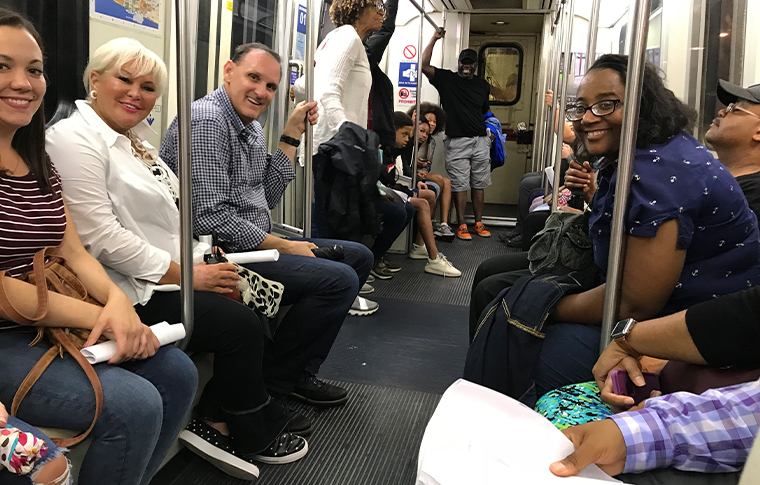 Group of people smiling and riding the metro