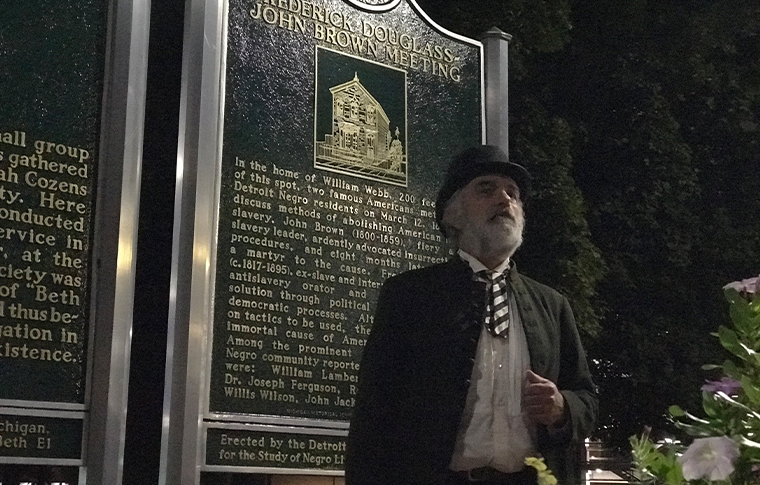 Actor in antiquated clothes posing in front of a sign reading 'Frederick Douglass John Brown Meeting'