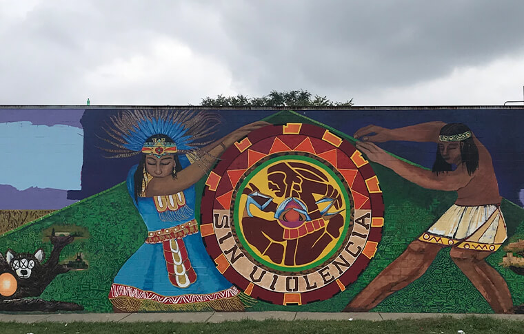 Colorful mural with two figures holding a seal that reads 'Sin Violencia'