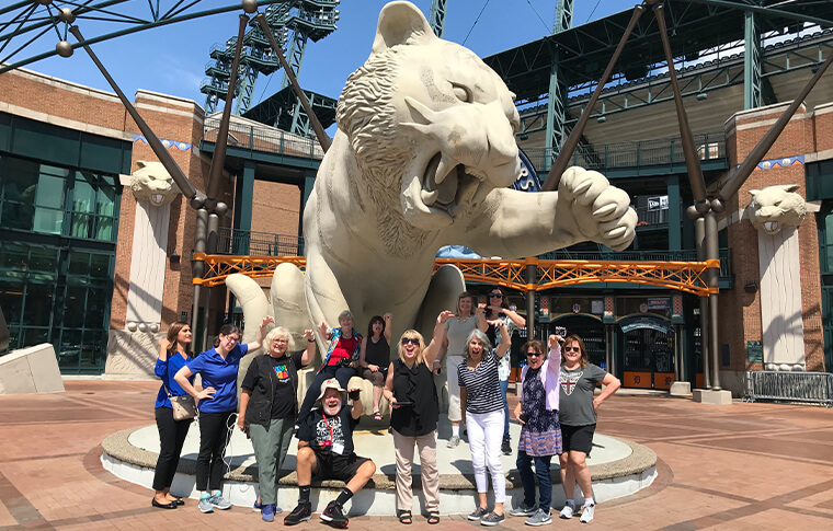 Group of adults with their arms outstretched mimicking the statue of a tiger with its paw outstretched behind them