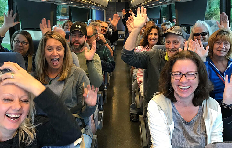 Group of adults with their hands up while seated on a bus, as seen from the inside