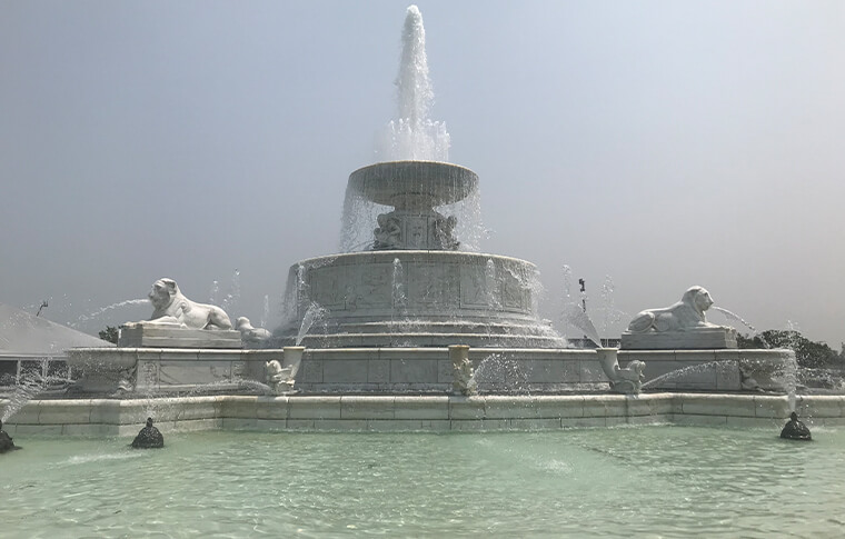 Large fountain with lions spitting out water alongside it