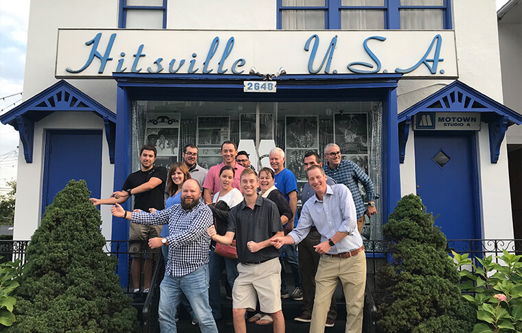 Group of adults posing in front of a building with a sign reading 'Hitsville USA' on it
