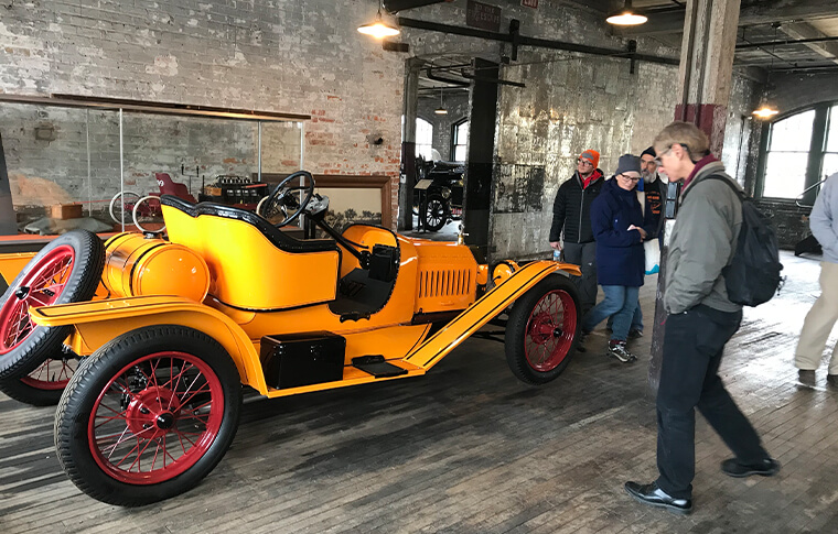 Group of people admiring a bright yellow antique car