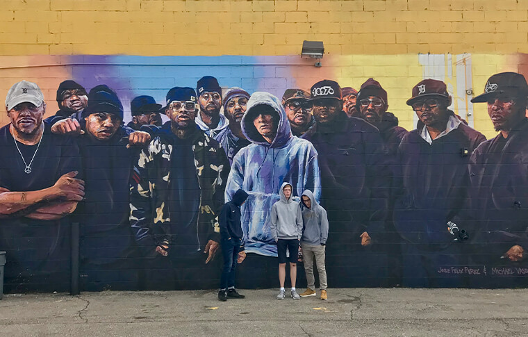 Group of men with hoodies drawn mimicking a mural of a crowd of hip hop artists behind them