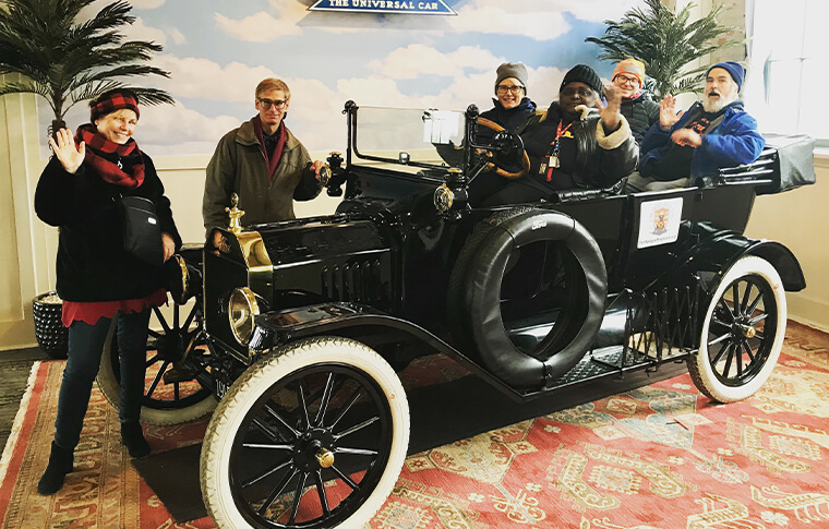 Group of adults posing in an antique car