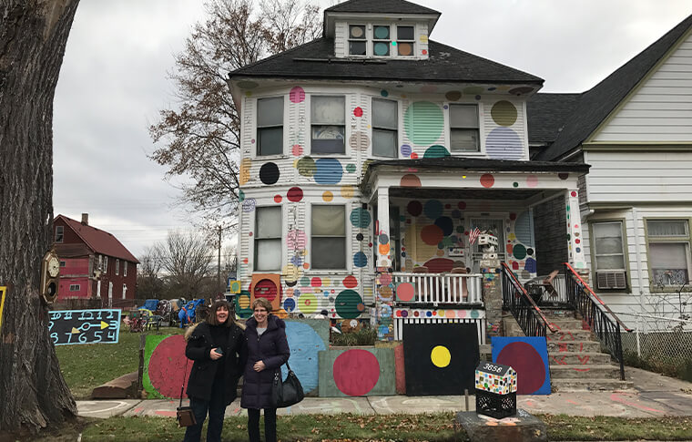 Two women posing in front of a house painted with polka dots