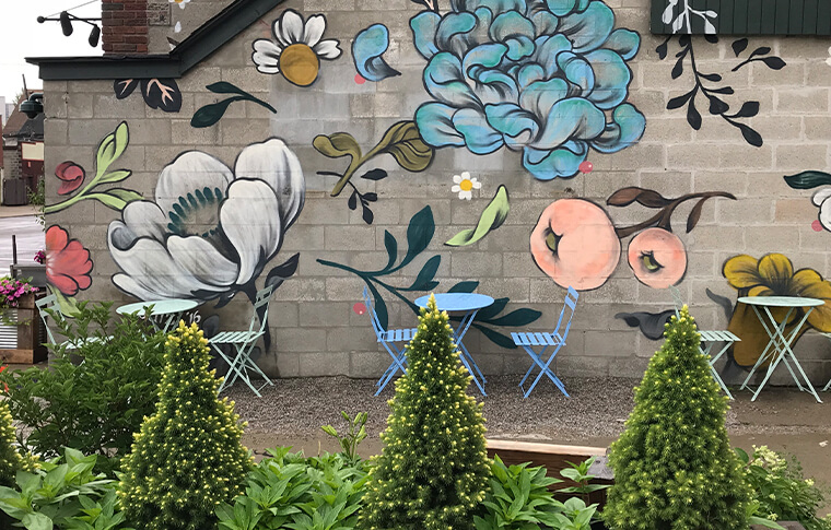 Mural of fruit and flowers with colorful dining tables in front