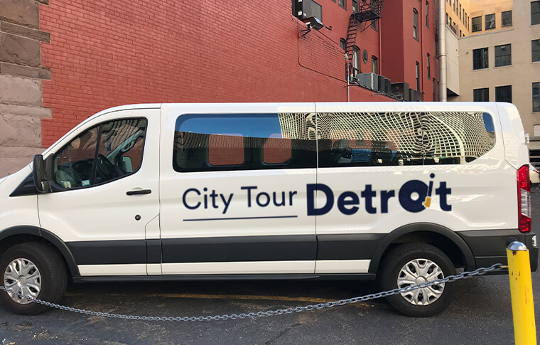 Large white van with City Tour Detroit printed on the side