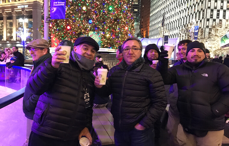 Group of men in winter coats holding up coffee cups in front of a large Christmas tree