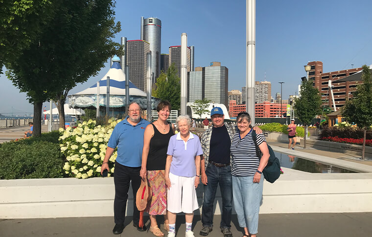 Group of five adults posing in front of the Detroit skyline