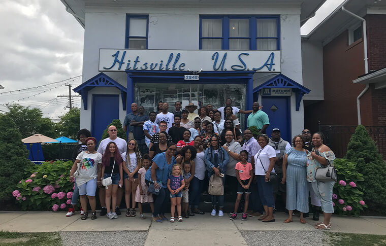 Group of guests posing in front of a building with a sign reading 'Hitsville USA' on it